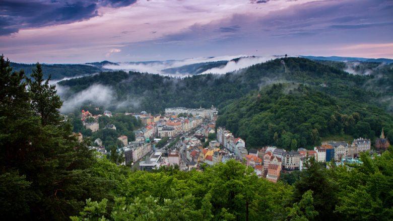 Karlovy-Vary - Blick auf die zwischen Hügeln liegende Stadt mit Wolken am Himmel
